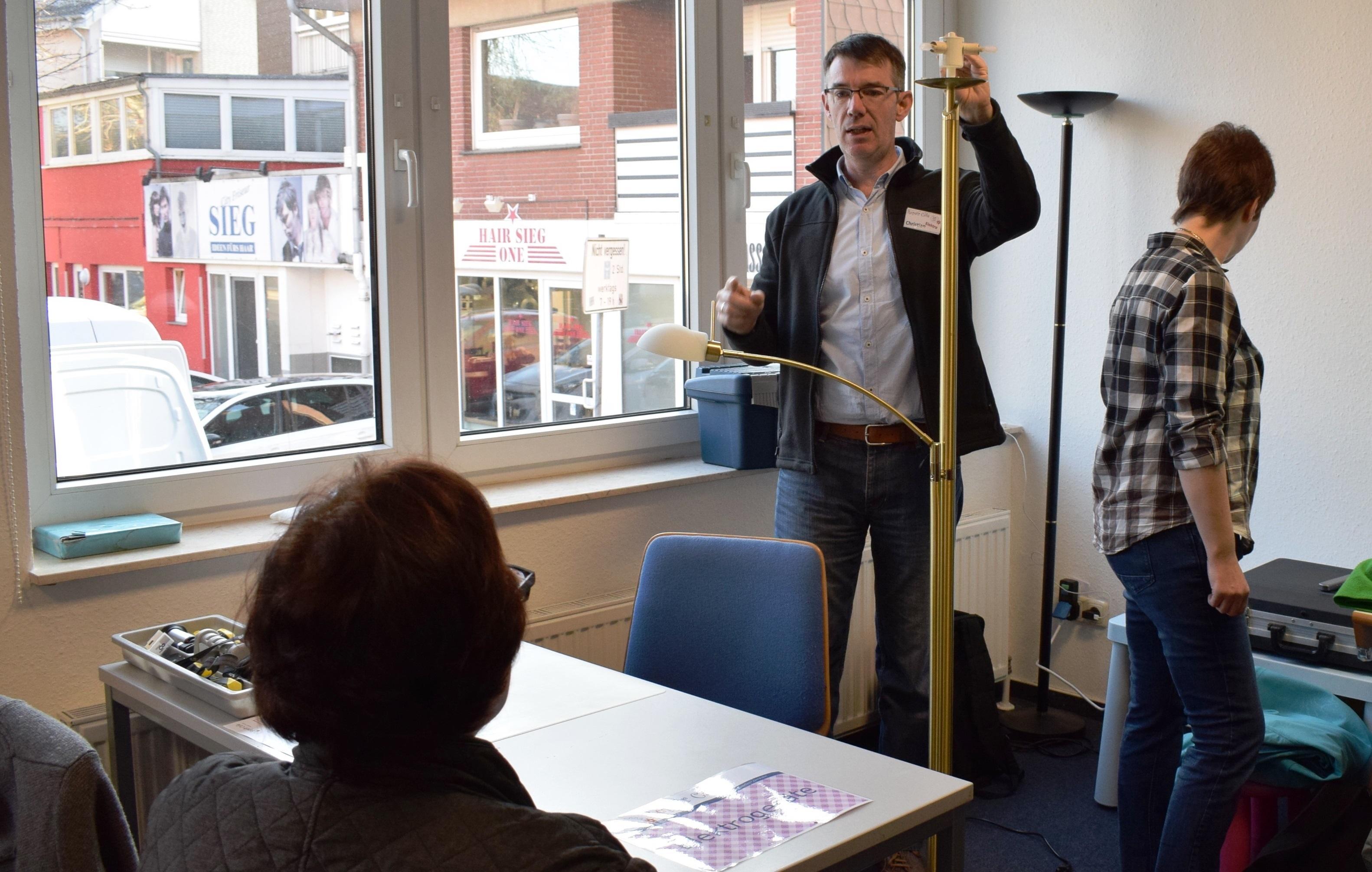 Christian Markhof (Mitte) repariert eine Stehlampe und erklärt der Besitzerin dabei jeden Schritt.