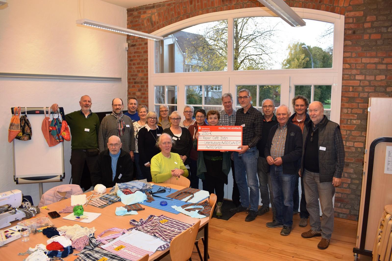 Einige der 22 ehrenamtlich Engagierten für das Repair Café Belm waren am vergangenen Freitag vor Ort und nahmen gemeinsam mit Fred Anders (5.v.r.) und Erika Rosenthal (7.v.r.) gern den AWIGO-Scheck entgegen.