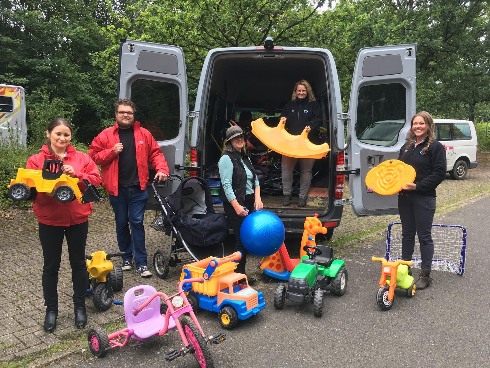 Auf dem Parkplatz des ZUE-Geländes in Ibbenbüren nahmen (v.l.n.r.) Derya Arslan und Sven Wilcke vom DRK-Betreuungsdienst die Spenden aus der AWIGO-Spielzeugaktion von Gabi Pehle, Daniela Treidel und Annett-Marie Krone begeistert entgegen.