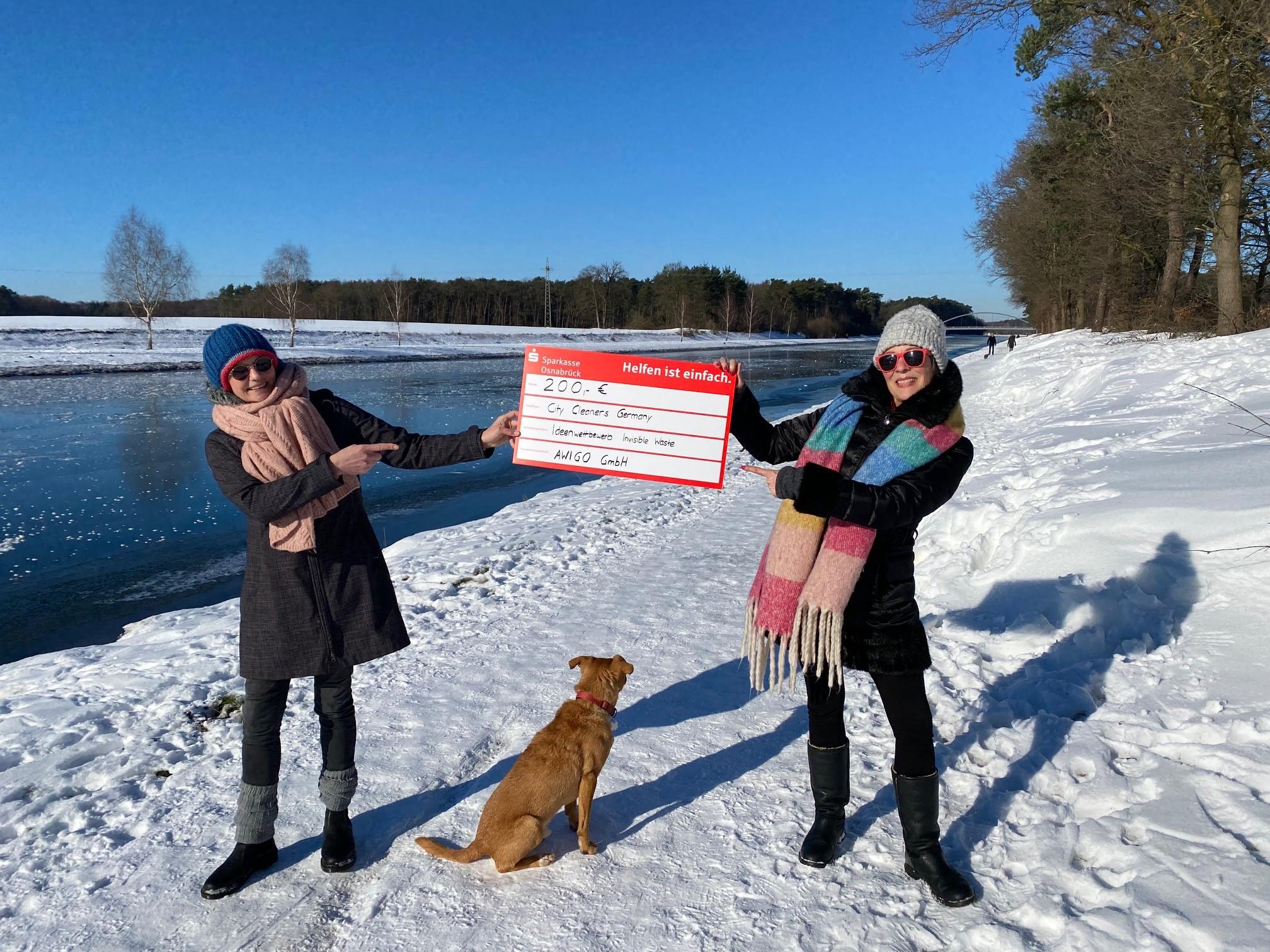 Am Kanal in Wallenhorst, einer ihrer Hauptsammelstrecken von achtlos weggeworfenem Müll, nahmen (v.l.n.r.) Barbara Schwermann, Hund Ronny und Birgit Schad für die City Cleaners Germany den Scheck über das Preisgeld entgegen.